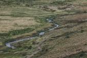 """Постер, картина, фотообои """"Аэрофотоснимок красивой реки, протекающей через высокогорье в Исландии"""""""
