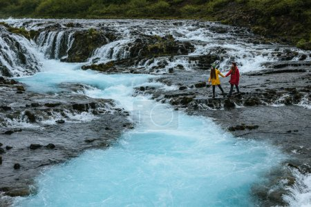 Photo for Two young women holding hands at Bruarfoss waterfall on Bruara river in Iceland - Royalty Free Image