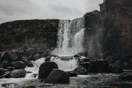 Photo pour Vue panoramique de la cascade dans les hautes terres sous un ciel nuageux dans le parc national de Thingvellir en Islande - image libre de droit