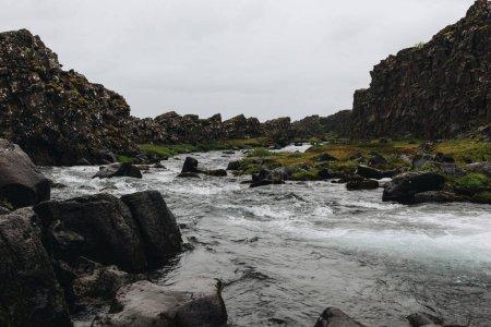 Photo pour Belle rivière de montagne qui coule à travers les hautes terres sous un ciel nuageux dans le parc national de Thingvellir en Islande - image libre de droit