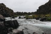 """Постер, картина, фотообои """"красивая горная река течет через высокогорье под пасмурным небом в Национальный парк Тингветлир в Исландии"""""""