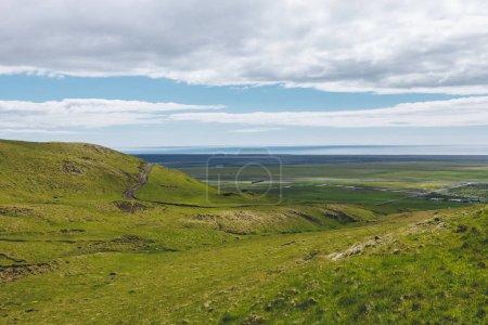 scenic view of landscape with green highlands under cloudy blue sky in Iceland