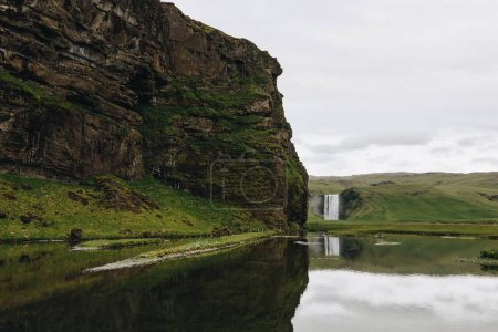 scenic view of beautiful waterfall Skogafoss in highlands under cloudy sky in Iceland