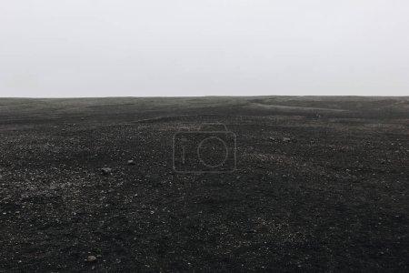 Photo pour Plein cadre de la plage de sable noir contre ciel nuageux à Solheimasandur, Islande - image libre de droit