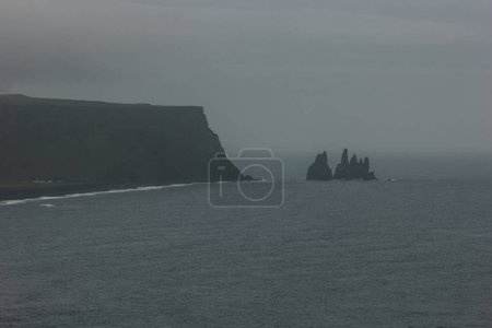 rocky cliff and ocean under cloudy sky at Dyrholaey promontory in Vik, Iceland