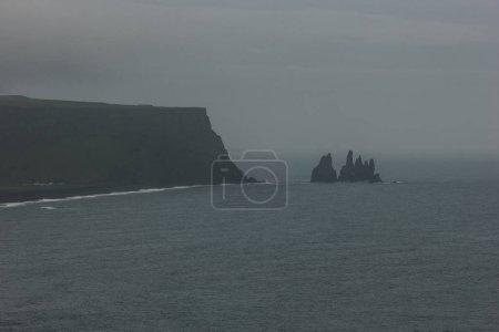 falaise rocheuse et océan sous un ciel nuageux au promontoire de Dyrholaey Vik, Islande