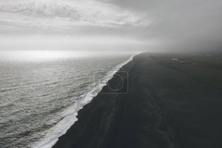Photo for Wavy ocean and coastline of black sand beach under cloudy sky in Vik, Iceland - Royalty Free Image