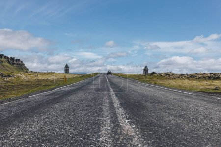 Photo for Road with car in highlands under blue cloudy sky in Iceland - Royalty Free Image