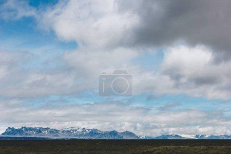 Photo pour Paysage avec des montagnes couvertes de neige sous un ciel nuageux en Islande - image libre de droit