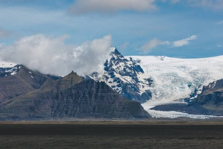 beautiful landscape with mountains covered by snow under blue cloudy sky in Iceland