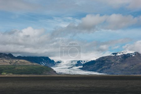 scenic view of landscape with mountains covered by snow under cloudy sky in Iceland