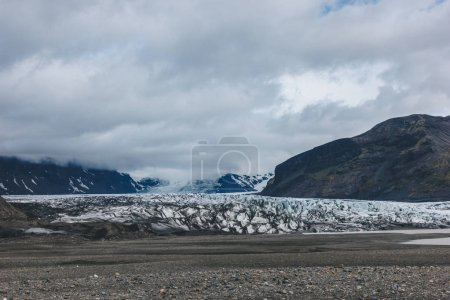 landscape with mountains covered by snow under cloudy sky in Skaftafell National Park in Iceland