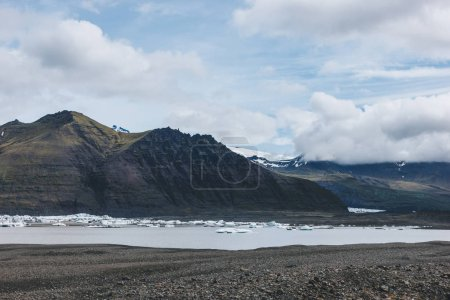 beautiful mountains and lake under cloudy sky in Skaftafell national park in Iceland