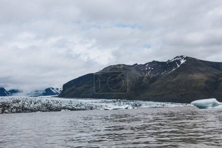 landscape with glacier Skaftafellsjkull and snowy mountains against cloudy sky in Skaftafell National Park in Iceland