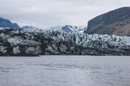 Photo pour Glacier Skaftafellsjkull et montagnes enneigées contre ciel nuageux dans le Parc National Skaftafell, Islande - image libre de droit