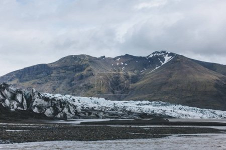 glacier Skaftafellsjkull and snowy mountains against cloudy sky in Skaftafell National Park in Iceland