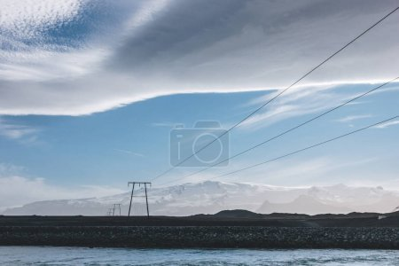 beautiful icelandic sky above high voltage wires and blue river, Jokulsarlon, Iceland