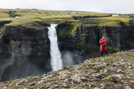 woman in red raincoat taking photo of Haifoss waterfall