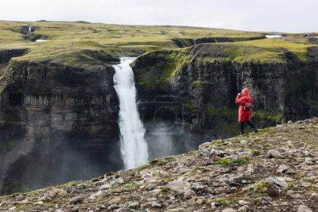 Photo pour Femme en prenant imperméable Rouge photo de cascade de Haifoss - image libre de droit