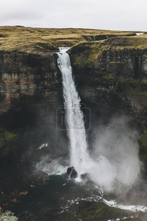 aerial view of icelandic landscape with Haifoss waterfall and green hills