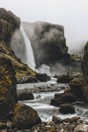 dramatic icelandic landscape with Haifoss waterfall on misty day