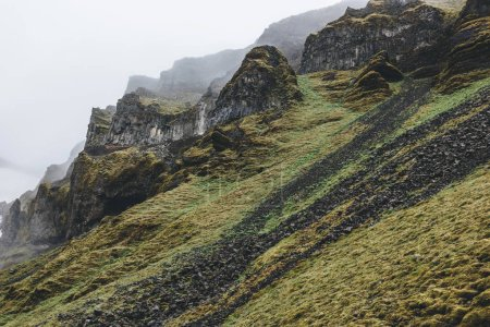Photo for Dramatic shot of mountain with green grass and rocks in Iceland on misty day - Royalty Free Image
