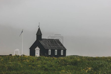 dramatic shot of Budir church on green field at Snaefellsnes, Iceland