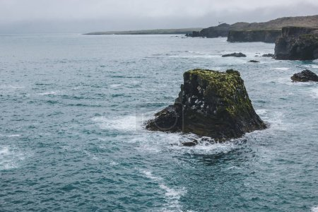 scenic shot of rocks and cliff in blue ocean in Arnarstapi, Iceland on stormy day
