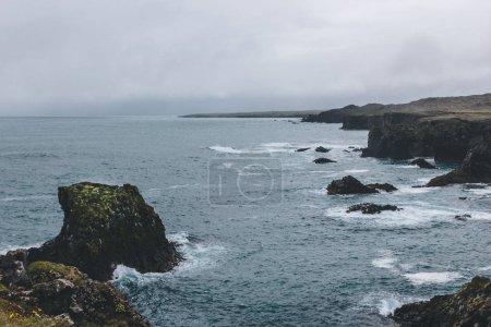 Photo pour Prise de vue spectaculaire de rochers et de falaises dans l'océan bleu à Arnarstapi, en Islande, le jour de tempête - image libre de droit