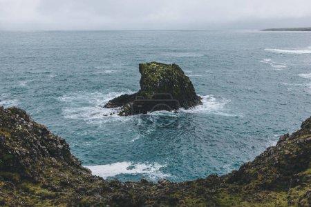 Photo pour Prise de vue spectaculaire de la roche dans l'océan bleu à Arnarstapi, Islande sur la journée orageuse - image libre de droit
