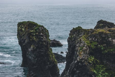 mossy cliffs in front of blue ocean in Arnarstapi, Iceland on cloudy day
