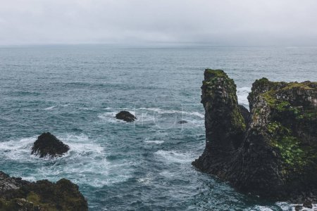 rocky cliffs in front of blue ocean in Arnarstapi, Iceland on cloudy day