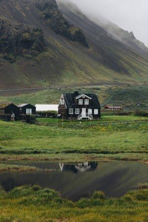 Photo pour Maison solitaire sur une colline verdoyante en Islande avec reflet dans l'étang - image libre de droit