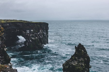 dramatic shot of rocky cliffs and stormy ocean in Arnarstapi, Iceland on cloudy day