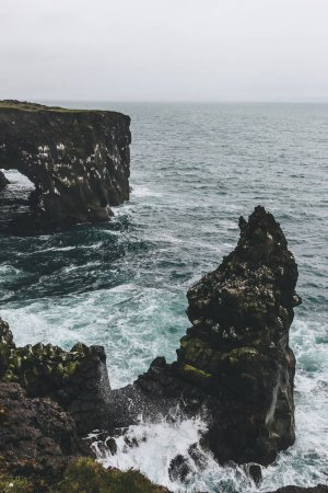 beautiful rocky cliffs and stormy ocean in Arnarstapi, Iceland on cloudy day