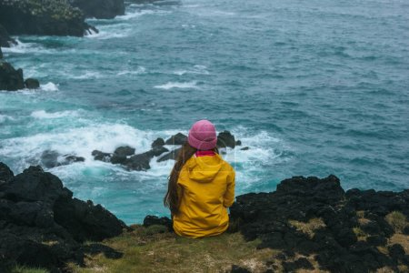 rear view of woman in yellow raincoat sitting on cliff in front of ocean, iceland