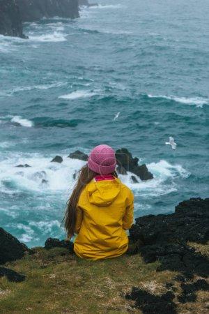 Photo pour Vue arrière de la femme en imperméable jaune assis sur une falaise en face de l'océan orageux, iceland - image libre de droit