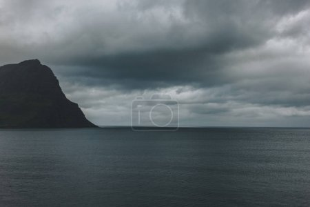 Photo pour Coup dramatique de l'océan bleu avec falaise en Islande sous un ciel orageux - image libre de droit
