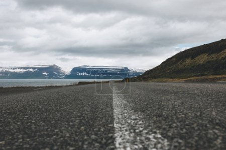 Photo for Empty asphalt road in Iceland with beautiful lake and mountains on background - Royalty Free Image