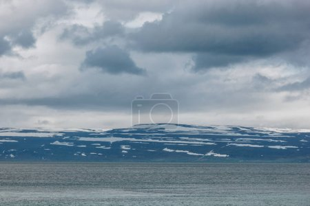 dramatic shot of lake under cloudy sky in Iceland with snowy mountains on background