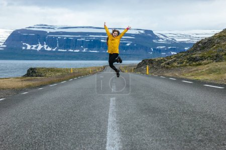 Photo for Young woman jumping on empty road in iceland with beautiful mountains and lake on background - Royalty Free Image