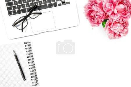 Feminine flat lay. Laptop, notebook, pink peony flowers. Office workplace