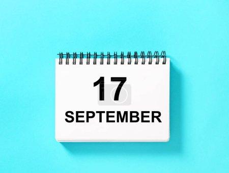 Photo pour Calendar book for date on blue background. 17 September calendar page - image libre de droit