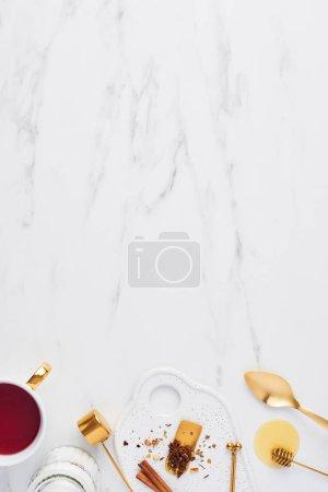 Photo pour Vue de dessus des ustensiles de thé blanc et or avec des herbes et du thé aux fruits sur fond de marbre blanc avec espace de copie. tasse de thé, plat laïc . - image libre de droit