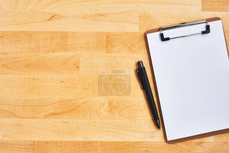 Presse-papiers et stylo en carton sur fond bois