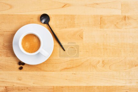 Photo for Cup of coffee or espresso with spoon and coffee beans on wooden table. Top view. Copy space for text. Flat lay. - Royalty Free Image