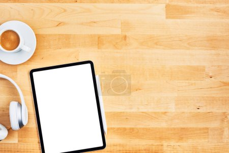 Photo for Digital tablet with blank white screen, pen, wireless headphone and cup of coffee on wooden office desk. Top view. Copy space for text or design. Flat lay. - Royalty Free Image