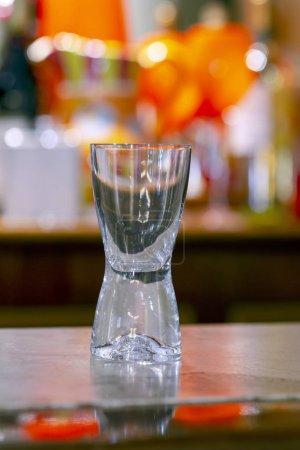 Foto de Copa vacía de licor sobre el contador de la barra de piedra con estantes en el fondo - Imagen libre de derechos
