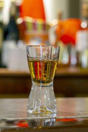Foto de Vaso de whisky en una piedra de la barra mostrador con estantes en el fondo - Imagen libre de derechos