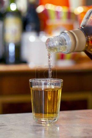 Foto de Whisky verter de la botella sobre cristal en piedra barra tabl - Imagen libre de derechos